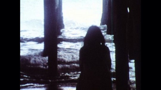 UNITED STATES: 1970s: girl walks under pier through water. Girl collapses in sea.