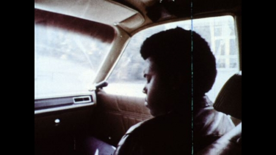 UNITED STATES: 1970s: young man sits in seat of car. Boy sits in Sheriff