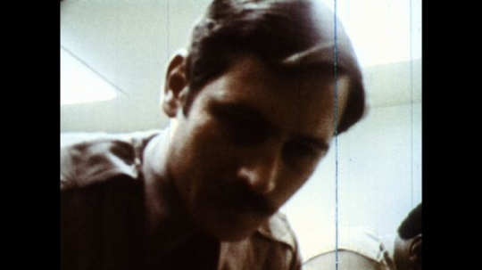 UNITED STATES: 1970s: police man talks to teenager in cell. Boy at police station