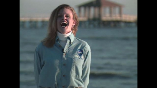 UNITED STATES: 1990s: female presenter introduces NASA Connect. Lady by sea.