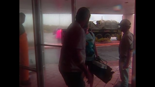 UNITED STATES: 1990s: people arrive at building before hurricane. Lady talks to camera. The Weather Channel sign. Broadcasters interview about weather prediction. Time lapse of clouds over city.