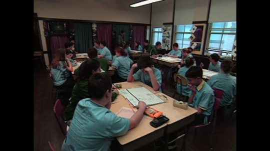 UNITED STATES: 1990s: students work in groups in classroom. Teachers and students talk to camera
