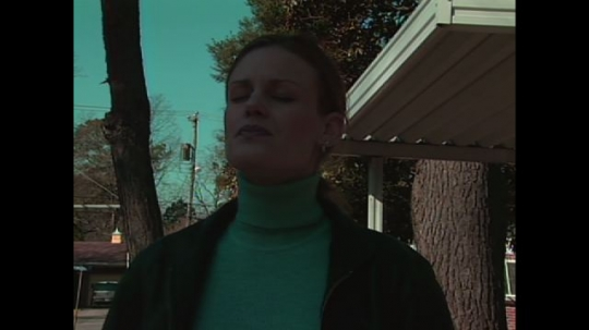 UNITED STATES: 1990s: lady with eyes closed in street. Sun moves over woman's face