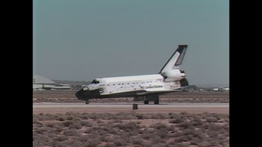 UNITED STATES: 1990s: space shuttle on runway. Astronaut stands inside space shuttle.