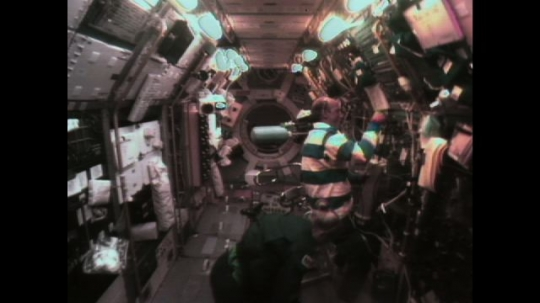UNITED STATES: 1990s: astronauts work in space shuttle. Astronaut drinks water