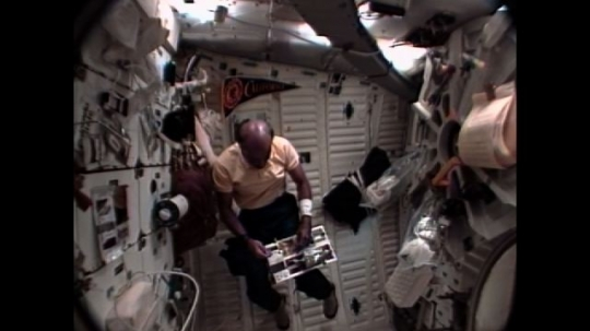 UNITED STATES: 1990s: astronaut catches objects in space. Astronauts do neurovestibular tests in space