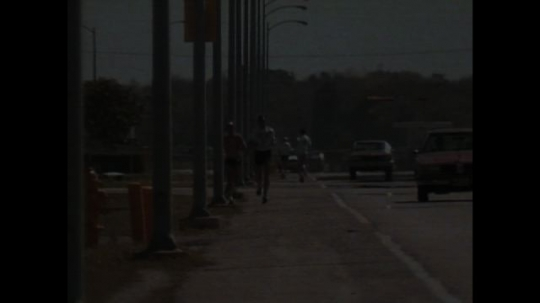 UNITED STATES: 1990s: people run along road by traffic. Man works out in gym