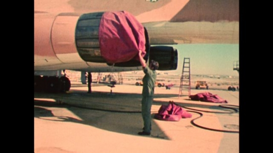 UNITED STATES: 1970s: man pulls cover off engine. Men work on B1 aircraft. Preparing a plane for flight
