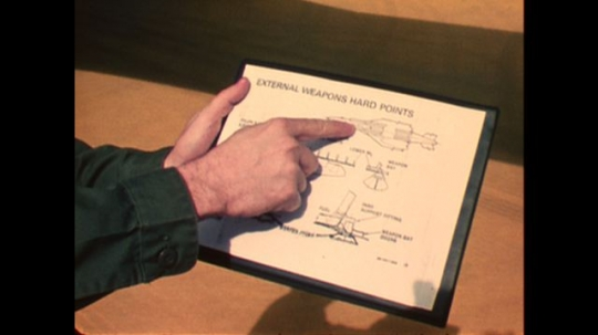 UNITED STATES: 1970s: man points to location of aircraft weapons on paper and on plane. Fuselage of plane. Nuclear bombs and launchers in plane.