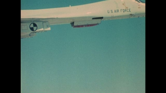 UNITED STATES: 1970s: missile dropped by plane in sky. Parachute on missile. Bullets fly from back of plane.