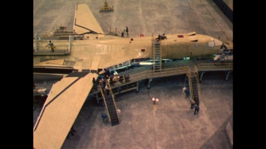 UNITED STATES: 1970s: plane in assembly park. Lady works on plane construction. Manufacture process of planes.