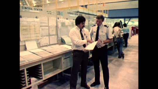 UNITED STATES: 1970s: air force men look over plane build plans. Man walks around plane in assembly plant.