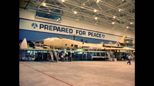 UNITED STATES: 1970s: prepared for peace sign on wall. Plane production park. Audience gives standing ovation at launch of plane. Window of plane.