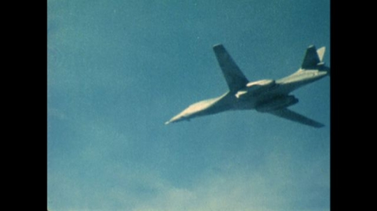 UNITED STATES: 1970s: view of plane from below as it flies. Plane flies over land.