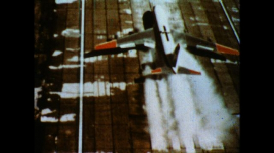 United States: 1980s: aircraft lands on runway view from above. Wet and dry runway. Machine travels across water.