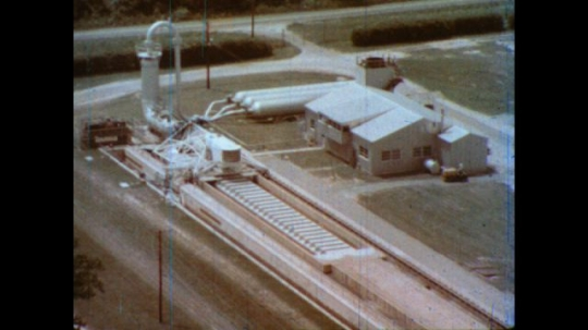 United States: 1980s: close up of research building. Explosion of water makes machine travel.