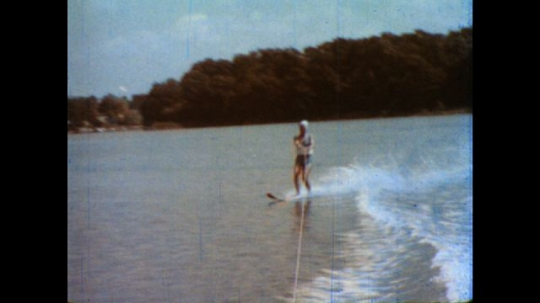 United States: 1980s: Lady water skis on lake. Lady crossing over wake of boat on water ski.
