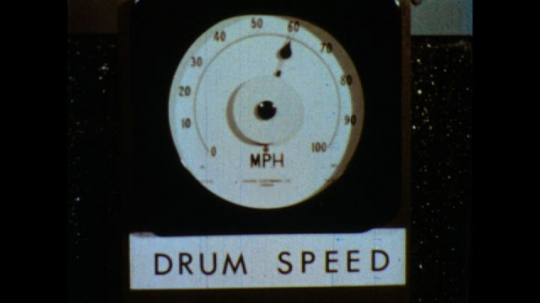 United States: 1980s: close up of drum speed machine. Close up of wheel in lab conditions. Wheel on wet surface. Man stops wheel spinning.