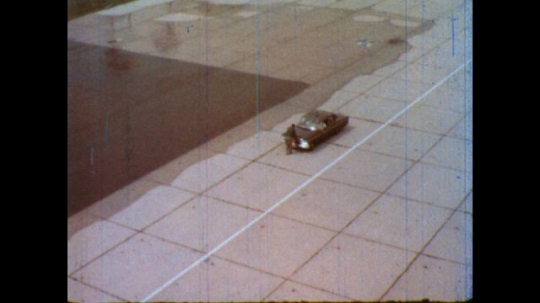 United States: 1980s: overhead view as man closes bonnet of car. View across wet surface.