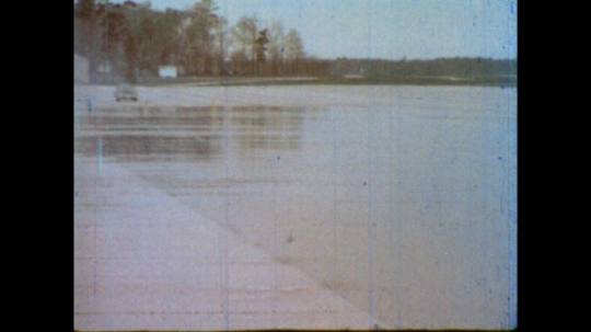 United States: 1980s: View from front as car travels across wet surface. Car brakes and slides across wet surface.