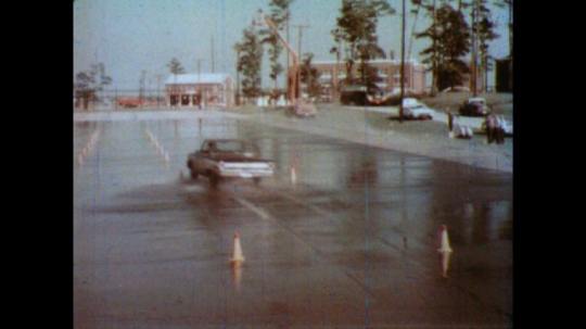 United States: 1980s: car slides as it drives through obstacle course on wet surface. Car hits traffic cones in test. Close up of wheel.
