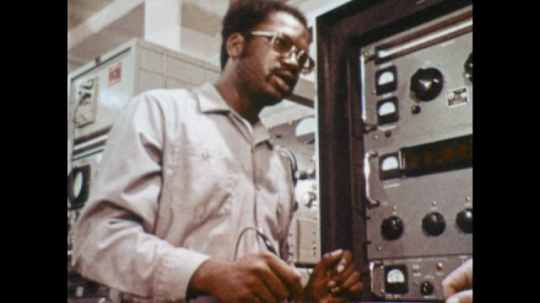 UNITED STATES: 1970s: Man learns electronics on machine. Navy ship at sea. Navy nuclear submarine at surface of water.