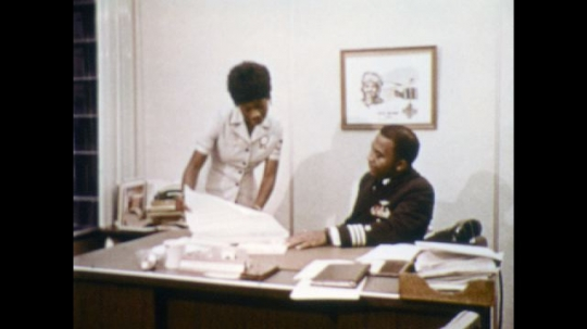 UNITED STATES: 1970s: Navy employees work in office. Lady shows paperwork to man at desk.  Female recruits in Navy learn electronics.