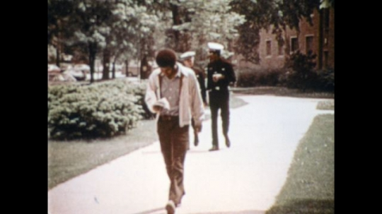UNITED STATES: 1970s: man walks along path and reads book. Navy men talk and chat during walk. Naval Reserve officers at university.