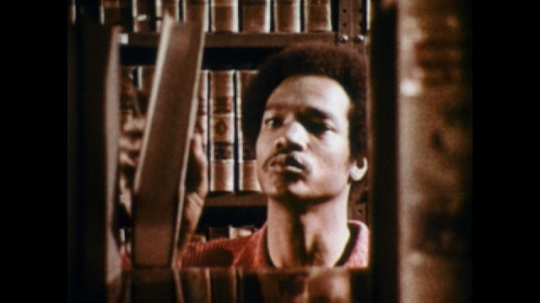 UNITED STATES: 1970s: man takes book off shelf. Man walks past shelf in library. Man smiles at colleague in library.