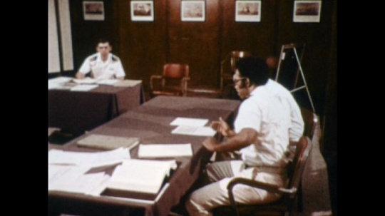 UNITED STATES: 1970s: Navy officer works as attorney. Navy lawyer in court room. Close up of Navy uniform lapel. Man works at desk. Man reads and writes notes
