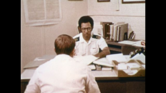 UNITED STATES: 1970s: Navy attorney talks to man at desk.