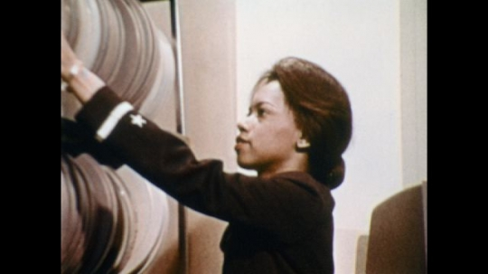 UNITED STATES: 1970s: close up of lady in Navy uniform. Lady takes film canisters from shelf.  Female Naval Officer presents to room. Lady points at map with stick.