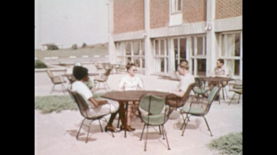 UNITED STATES: 1970s: people sit at table in yard. Lady opens door of apartment. Boys arrive at party. Lady greets man. Navy Officer Candidate School flag blows in wind. Navy students in class.