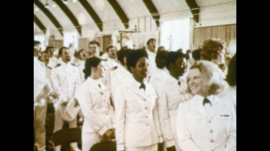 UNITED STATES: 1970s: navy graduates throw caps in air. Lady claps and smiles. Lady puts graduation cap on boy's head. Man smiles and feels graduation cap.