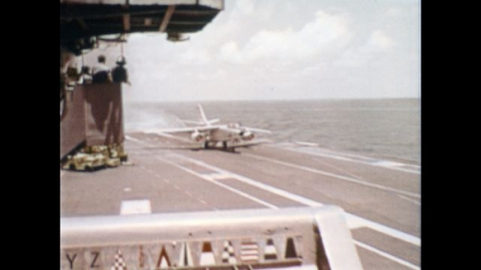 UNITED STATES: 1970s: fast jet lands on aircraft carrier. Wings raise on plane. Helicopters in air. Pilot climbs down from plane.