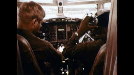 UNITED STATES: 1970s: Navy pilot puts on headset in cockpit of plane. Naval flight officer training in plane. Student learns about plane electronics. Navy recruit looks at charts.