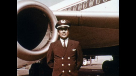 UNITED STATES: 1970s: Man in uniform stands next to engine of plane. Man talks to camera. Pilot inspects plane. Front view of plane on ground