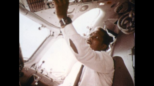 UNITED STATES: 1970s: commercial pilot inside cockpit of plane. Man checks buttons and dashboard inside plane