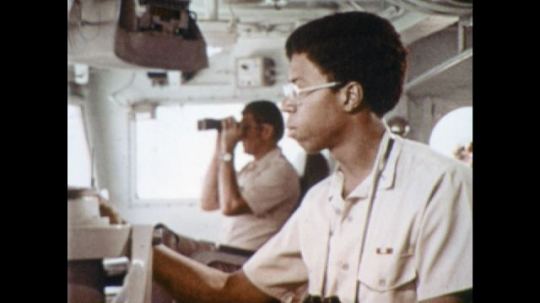 UNITED STATES: 1970s: Navy men work on bridge of ship. Man looks through binoculars. Man looks closely at ship navigation. Side profile of face of man on ship.