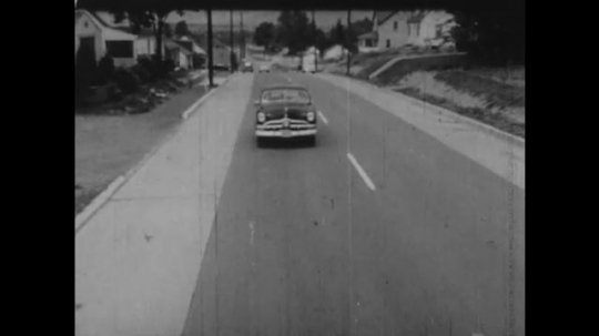 United States: 1950s: car drives along road. View from front. Car swerves across road. Car overtakes on road. Man walks along sidewalk. Stop sign at side of road.