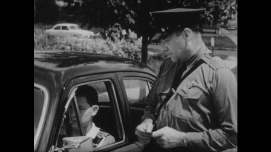 United States: 1950s: policeman nods head. Boy in car lowers head. Close up of boy talking.