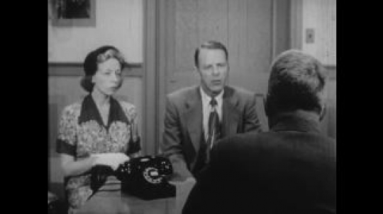 United States: 1950s: man talks to man sat at desk. Lady looks at man. Parents talk to officer. Side view of lady in station. Boys look before crossing road.