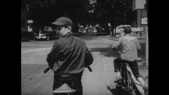 United States: 1950s: Boys ride bikes on road. Boy calls friend back. Boy on bike checks for traffic. Boy and parents sit in police office.