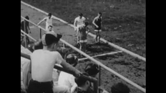 United States: 1950s: boys limber up for running race. Boys joke at start of race. Boys at starting blocks. Boy trips.