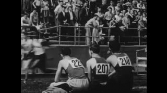 United States: 1950s: boys run race on track. Athletes watch runners from bench. Family interviewed in office.