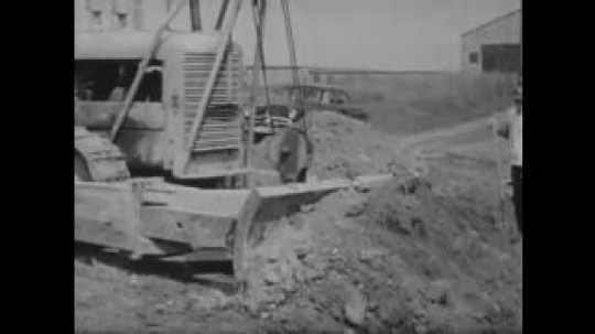 United States: 1950s: digger moves earth. Man drives car. Man talks to boy and parents in office. Side view of people in meeting.