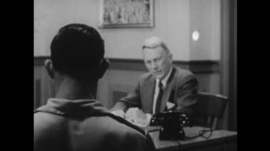 United States: 1950s: view of man from behind boy's shoulder. Man talks to boy, side view of family in meeting.