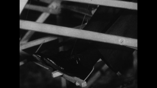 United States, 1910s: close up of feet on pedals. Foot taps on floor. Close up of hands on levers. Hands pull levers. Tail of plane moves when levers pulled. Plane tail.
