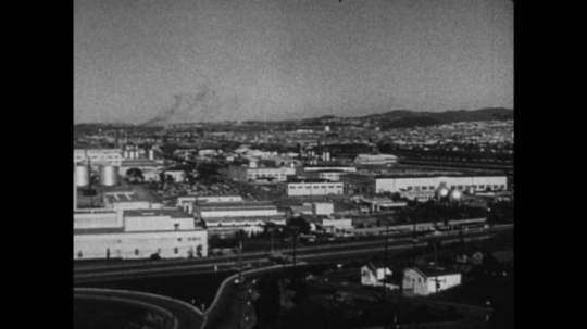 United States, 1940s: panoramic view across city. View across factory buildings. Close up of plane propeller.