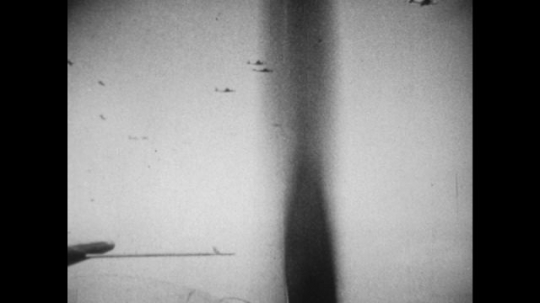 United States, 1940s: planes in sky during war. View of ground from bomber plane. Plane drops bomb on ground, view from plane. Plane flies over land.
